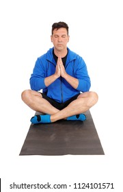 A meditating man in a blue jacket sitting on the floor in a yoga pose