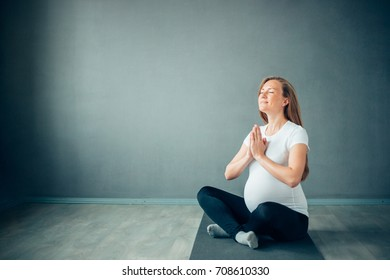 Meditating on maternity. Close-up of pregnant woman meditating while sitting in lotus position