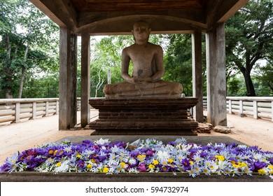 The meditating Samadhi Buddha Statue with the colorful lotus flowers on the altar, Anuradhapura, Sri Lanka.
