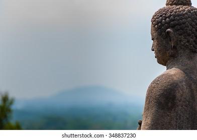 Meditating sitting Buddha in stone above jungle at Borobudur in Java, Indonesia