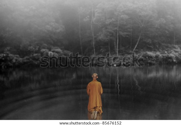 A meditating spiritual buddhist monk in orange robe kneeling on the surface of a lake in a surreal misty forest surrounding, while seeking atonement.