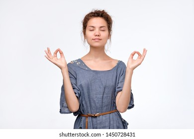 Meditation concept. Beautiful young woman stands in meditative pose, enjoys peaceful atmosphere, holds hands in mudra sign. Studio shot