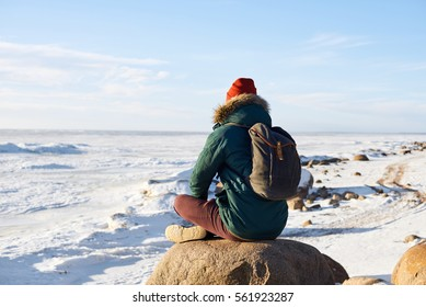 Meditation concept. Man have relax after hard journey. Guy look far to the horizont. Open space. Free place for advertising travel goods or tourism stuff. Winter landscape with frozen sea