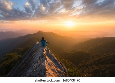 Meditation in great serenity at the top of a mountain rock in Taichung in Taiwan in front of the sun at sunset for great well being and wellness and energy