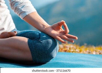 Meditation healthy life exercise concept - Close up of woman in Padmasana yoga lotus pose with chin mudra outdoors with copyspace. Teal orange color grading