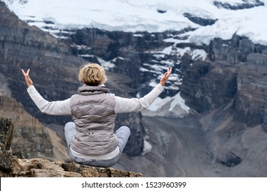 Meditation in mountains. Woman meditating on rock in front of rocks with glaciers and snow. Fairview Mountain top in Lake Louise area. Banff National Park. Alberta. Canada.