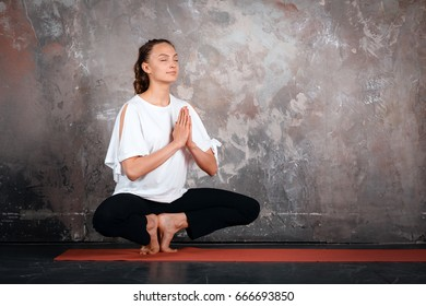 Meditation practicing yoga woman health, with closed eyes, urban gray background, indoor, copy space, gray wall