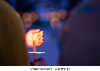 Meditation spirit concept, Candle on hand holding. Candle burning on bokeh light and blurred black background. Right hand holding it and left hand protect wind blowing it for burn growing  on night
