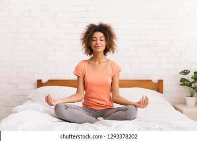 Meditation. Woman sitting in lotus pose on bed in the morning at home
