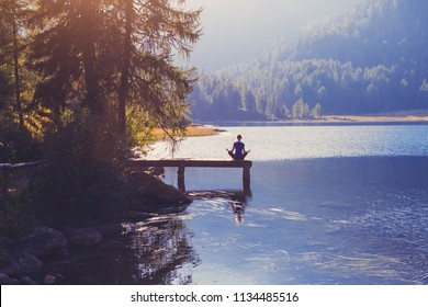 meditation and yoga practicing at sunset, breathe exercise background with silhouette of woman, calmness and harmony