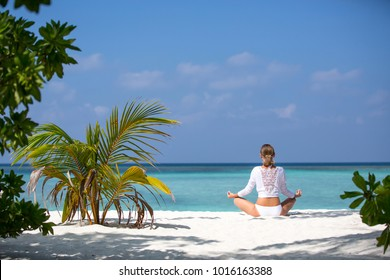 Meditation Yoga woman meditating at serene tropical beach. Girl relaxing in lotus pose in calm zen moment at ocean water. Multiracial girl Slim body tanned model. Health and fitness retreat concept