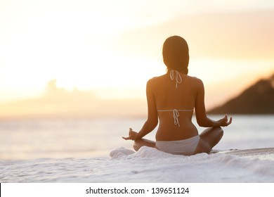 Meditation - Yoga woman meditating at serene beach sunset. Girl relaxing in lotus pose in calm zen moment in the ocean water during yoga holidays resort retreat. Multiracial girl.