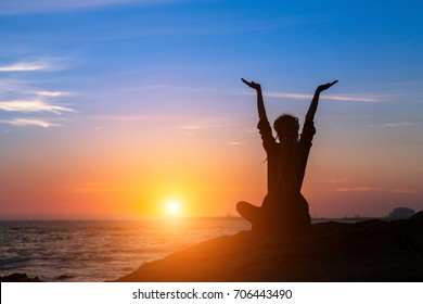 Meditation yoga woman silhouette on the Sea during amazing sunset. Healthy lifestyle.