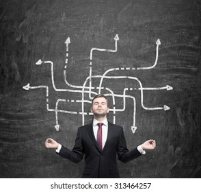Meditative handsome businessman is pondering about possible solutions of the complicated problem. Many arrows with different directions are drawn around his body. Black chalkboard as a background.