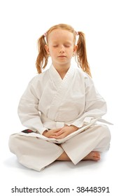 Meditative little girl in the karate school, isolated on white