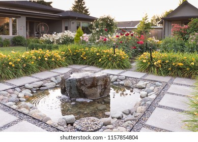 A meditative stone fountain hidden in a backyard garden.