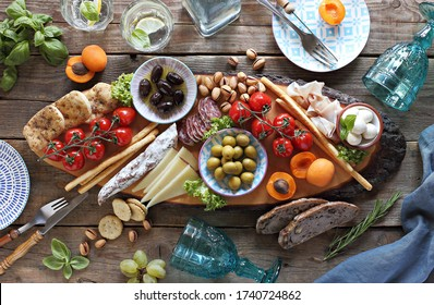 Mediterranean appetizers platter. Diner table with antipasto selection: cured meat and salami, gazpacho soup, jamon, olives, cheese, hummus and vegetables.   Overhead view.