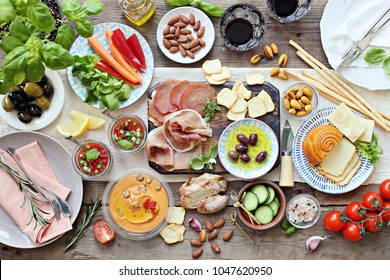 Mediterranean appetizers table concept. Diner table with antipasto selection: cured meat and salami, gazpacho soup, jamon, olives, cheese, hummus and vegetables.   Overhead view.