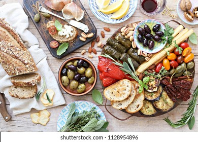 Mediterranean appetizers table concept.   Platter with antipasto selection, grilled vegetables, olives, nuts and roasted bread.  Overhead view.