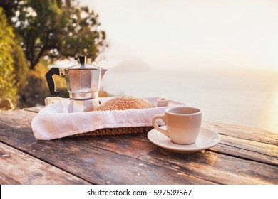 Mediterranean breakfast, cup of coffee and fresh bread on a table with trees and sea view at the background