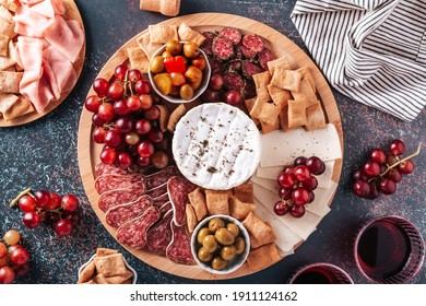 Mediterranean charcuterie board with various kinds of snacks for sharing on concrete background, top view