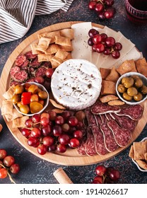 Mediterranean charcuterie board with various kinds of snacks for sharing on concrete background overhead