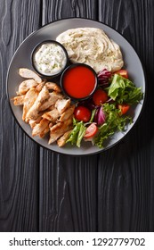Mediterranean Chicken Shawarma Bowl with hummus, vegetables salad and sauce close-up on a wooden table. Vertical top view from above