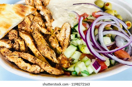 Mediterranean Chicken Shawarma Rice Bowl with Hummus Greek Salad Olives and Pita Bread Top View on Table