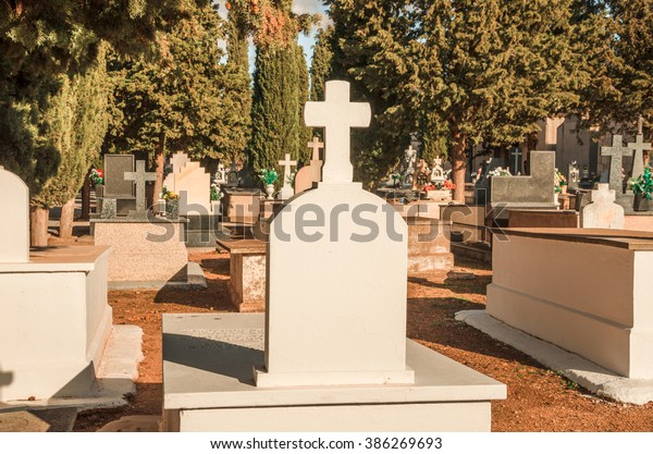 Mediterranean country graveyard - Spanish graveyard with white crosses on tombs and cypresses.