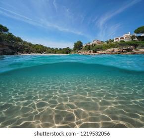 Mediterranean cove with houses and sand underwater sea, split view half above and below water surface, Costa Dorada, Spain, Cala Estany Tort, Catalonia, L'Ametlla de Mar, Tarragona