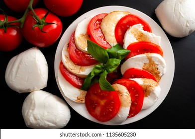 Mediterranean cuisine, fresh vegetarian food and italian culinary art concept with Caprese salad made of mozzarella cheese, rraw tomatoes and basil leafs isolated on black background