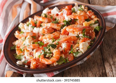 Mediterranean cuisine: shrimp Saganaki with feta cheese and tomatoes close-up on a plate. Horizontal
