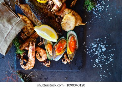 Mediterranean cuisine. Tasty sea food with shrimps and oysters on a dark stone table. Dish from the chef.