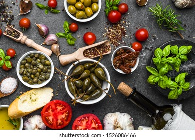 Mediterranean diet background. Cooking ingredients on dark slate.