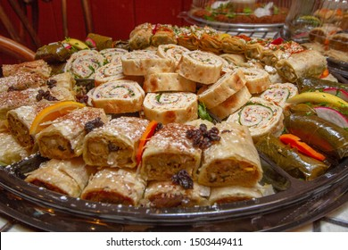 Mediterranean filo dough specialties, including chicken cilicia, dolmas, and Levant sandwiches on a platter as seen from above.