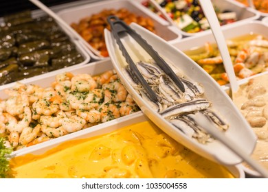 Mediterranean fish and antipasti on a street market decorated with green salad and aubergine vegetables in white porcelain plates