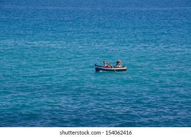 Mediterranean fishermen on a boat in the blue sea in sunny summer day