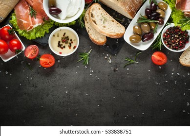 Mediterranean Food background. Ciabatta bread jamon serrano tomatoes herbs and olives on black slate board. Top view