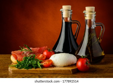 mediterranean food with mozzarella cheese, prosciutto, rucola, tomatoes and olive oil