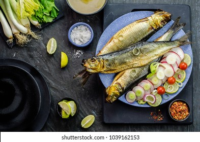 Mediterranean food, smoked Herring fish served with green onion,lemon,spices,cherry tomatoes,bread and Tahini sauce on dark background.Top view with close-up
