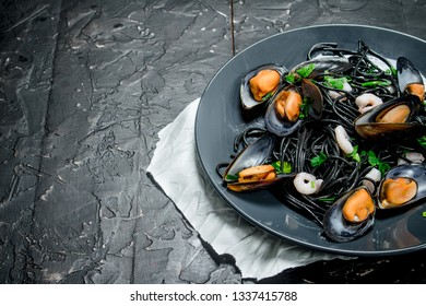 Mediterranean food. Spaghetti with cuttlefish ink and clams. On black rustic background.