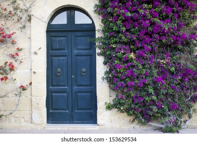 A mediterranean house in Gozo, Malta with an old door and a tree with flowers climbing the wall