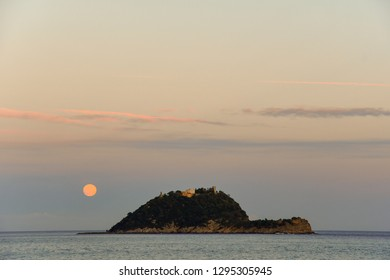 Mediterranean island at sunset with full moon and dramatic sky, Gallinara Island, Alassio, Liguria, Italy