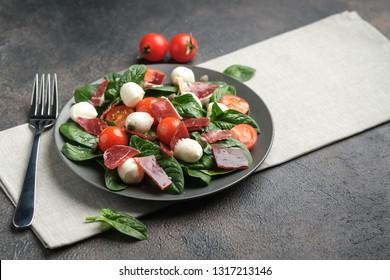 Mediterranean Kitchen. Fresh salad with arugula, mozzarella, prosciutto and capers on a dark background top view copy space.