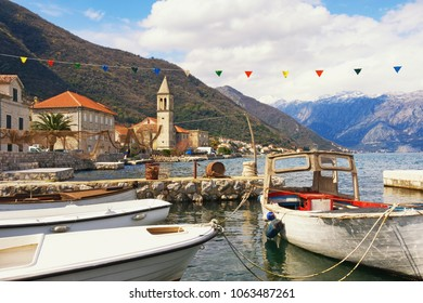 Mediterranean landscape with fishing boats in small harbor. Montenegro, view of Bay of Kotor and Stoliv town with Name of Mary Church