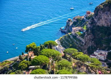 A mediterranean landscape with rocky coastal line of Amalfi coast, Italy, and a boat traveling in the sea along the coast