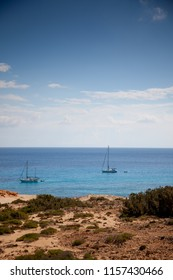Mediterranean landscape with the sea and some sailboats in the background under a blue sky with clouds