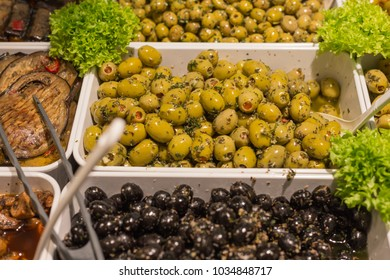 Mediterranean olives and olive paste on a street market decorated with green salad and aubergine vegetables in white porcelain plates