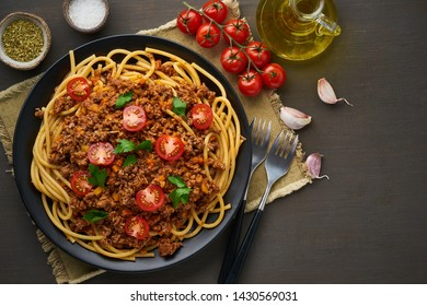 mediterranean pasta bolognese bucatini with mincemeat, tomatoes, carrot and basil leaves