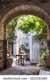 Mediterranean patio garden with table and chair, old stone ach and green trees.